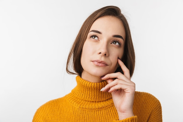 Attractive pensive young woman standing isolated over white wall