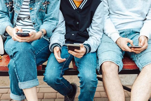 다양한 연령대의 매력적인 사람들이 스마트 폰을 사용합니다.