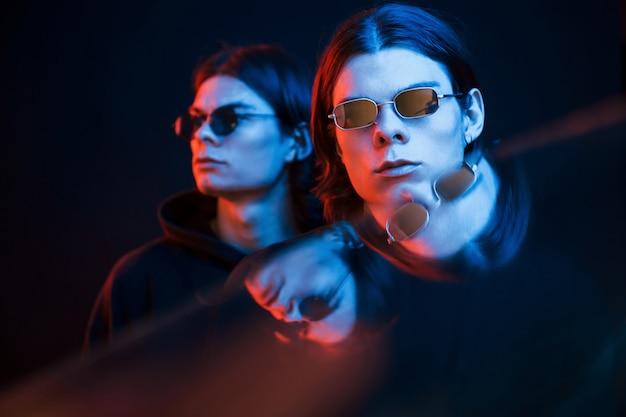 매력적인 사람들. 쌍둥이 형제의 초상화입니다. 네온 불빛이있는 어두운 스튜디오에서 촬영 한 스튜디오
