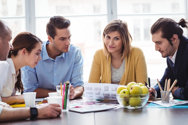 Attractive photo editor with coworkers in meeting room