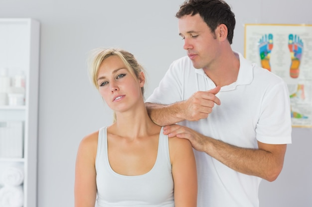 Attractive physiotherapist massaging patients neck with elbow