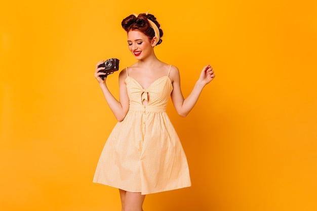 카메라를 들고 드레스에 매력적인 핀 업 소녀입니다. 노란 공간에 고립 된 웃는 여성 사진 작가의 스튜디오 샷.