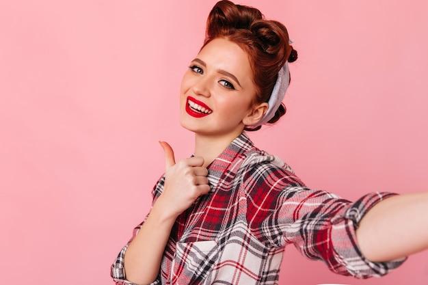 親指を立てて見せている魅力的なピンナップガール。ピンクの空間で自分撮りをしている生姜の若い女性のスタジオショット。