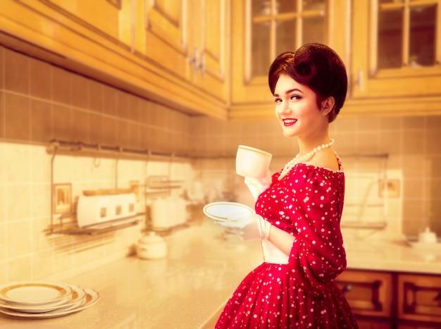 メイクアップと魅力的なピンナップガールは、50のアメリカンファッションのキッチンカフェでコーヒーを飲みます。ビンテージスタイルの水玉模様の赤いドレス