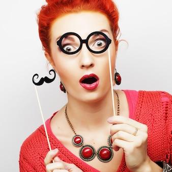 막대기에 콧수염과 안경을 들고 매력적인 쾌활 한 젊은 여자. 파티 준비.