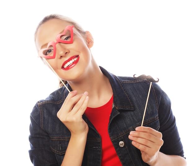 Привлекательная игривая молодая женщина, держащая усы и очки на палочке. готов к вечеринке.