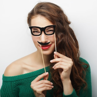 Attractive playful young woman holding mustache and glasses