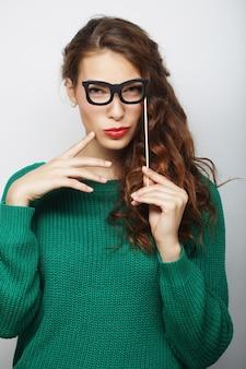 Привлекательная игривая молодая женщина в накладных очках, готовая к вечеринке