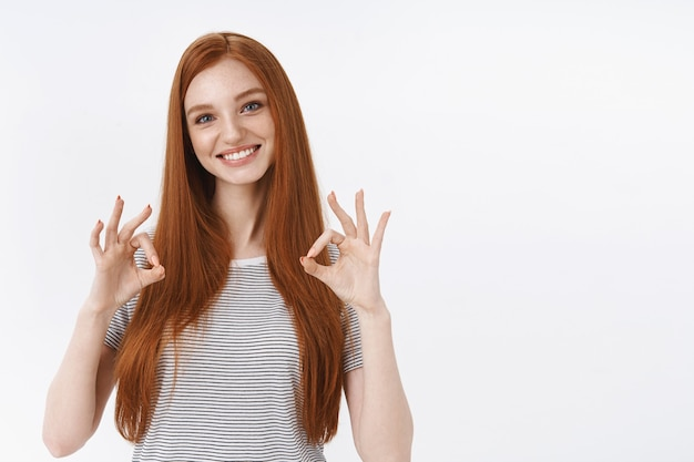 Attractive pleasant friendly-looking redhead teenage girl blue eyes tilting head amused show ok perfect gesture give approval affirmative reply liking good result, white wall