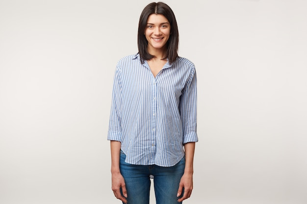 Привлекательная приятная молодая темноволосая женщина, стоящая в джинсах и полосатой рубашке. очаровательная милая позитивная девушка изолирована