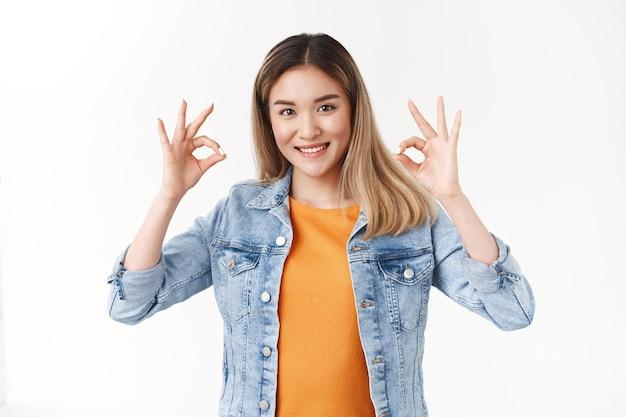 Привлекательная довольная азиатская студентка показывает хорошо, хорошо, жест подтверждения наслаждайтесь идеальной вечеринкой, широко улыбаясь, в джинсовой куртке, оранжевой футболке