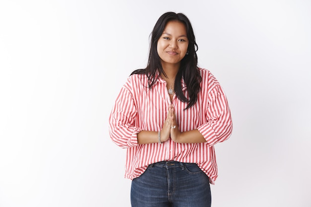 Attractive polynesian young 20s woman in striped blouse press palms together in polite greeting gesture saying namaste bowing to welcome dear guest smiling pleasantly over white wall