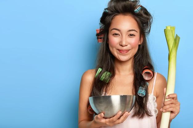 Привлекательная позитивная азиатская дама держит зеленый лук-порей, стальную миску, собирается нарезать овощи
