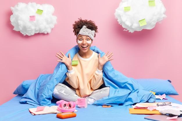 Привлекательная позитивная студентка реагирует на потрясающие новости, держит ладони поднятыми, готовится к экзаменам дома, позирует на кровати с бумагами