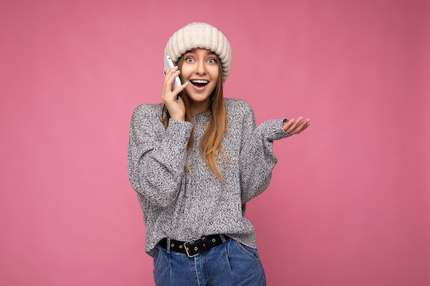 매력적인 긍정적 인 행복 놀라게 젊은 금발의 여자 캐주얼 회색 스웨터와 베이지 색 모자를 입고 분홍색 손에 들고 카메라를보고 휴대 전화에 통신 이상 격리.