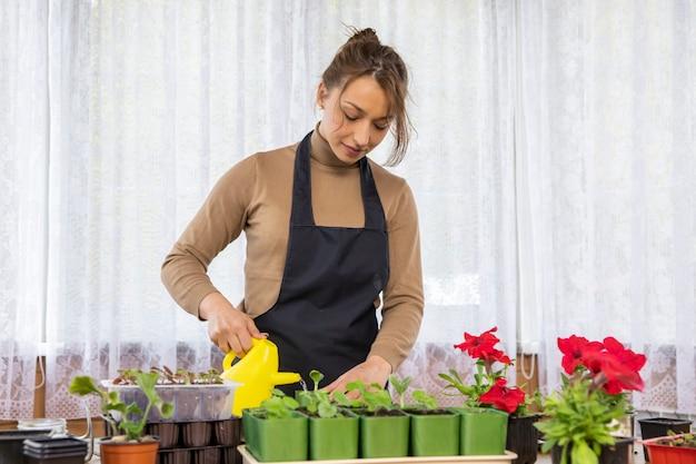 植え付け後のじょうろで花に水をまく魅力的なポジティブな楽しい女性