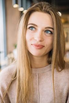 Привлекательная положительная задумчивая молодая женщина в кафе