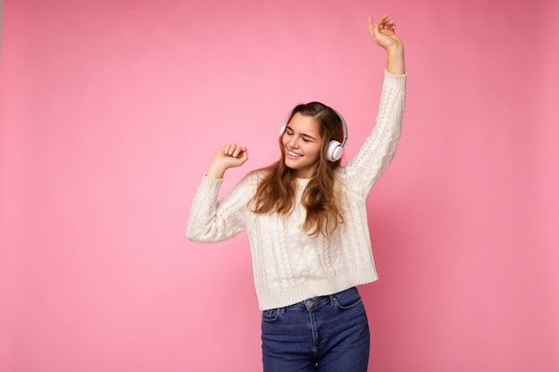 ピンクの背景の壁に分離された白いセーターを着てクールな音楽を聴いて移動する白いbluetoothイヤホンを身に着けている魅力的なポジティブな笑顔の若いブルネットの巻き毛の女性。フリースペース