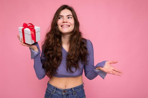 매력적인 긍정적 인 웃는 젊은 갈색 머리 여자 선물 상자를 들고 측면을 찾고 매일 유행 옷을 입고 화려한 벽 위에 절연.