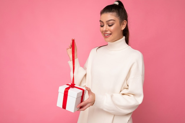 Attractive positive surprised young brunette woman isolated over pink background wall wearing white sweater holding gift box and unboxing present looking at box.