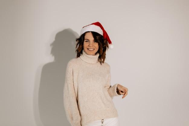 Привлекательная позитивная женщина в хорошем настроении позирует в шляпе санта