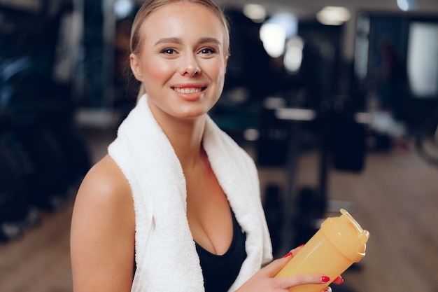 Attractive positive woman with towel and water bottle in gym