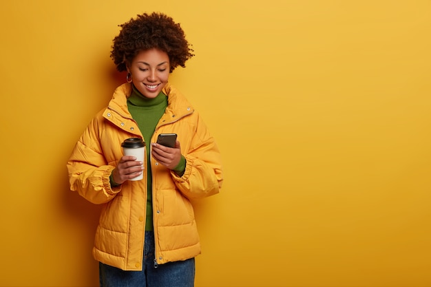 Attractive positive woman in yellow outerwear, happy to read good comments under post, holds modern cellphone, drinks takeout coffee