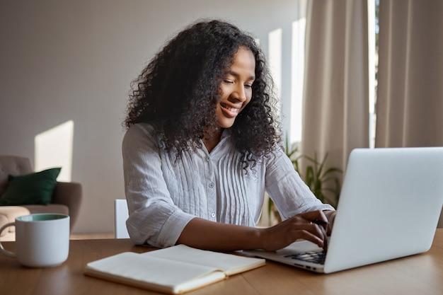 魅力的なポジティブな若いアフリカ系アメリカ人女性フリーランサーは、リモートで作業し、一般的なラップトップでキーボード操作し、コピーブックとマグカップをテーブルに置いて家に座って、オンラインで電子メッセージを入力し、笑顔