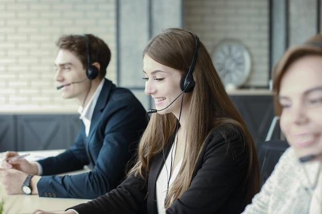 Привлекательные позитивные молодые бизнесмены и коллеги в офисе call-центра