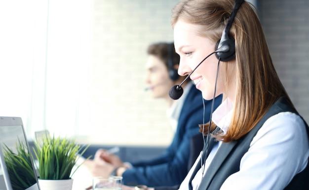 Привлекательные позитивные молодые бизнесмены и коллеги в офисе call-центра.