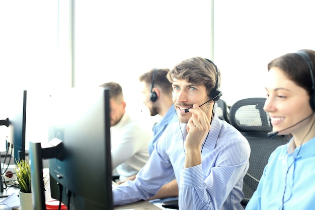 콜 센터 사무실에서 매력적인 긍정적인 젊은 기업인과 동료.