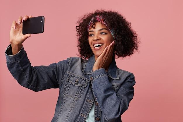 Привлекательная позитивная молодая кудрявая брюнетка с темной кожей, широко улыбающаяся и держащая ладонь на щеке, делая селфи на своем смартфоне