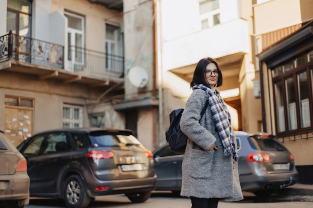 Attractive positive young girl wearing glasses in a coat on the background of buildings on cars