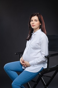 Attraente donna incinta con i capelli scuri seduta su una sedia nera e sorridente alla telecamera, immagine isolata su sfondo nero