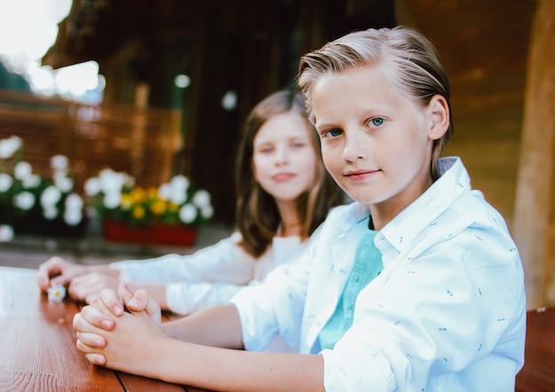 Привлекательный предподростковый белокурый мальчик с голубыми глазами в белой рубашке с сестрой
