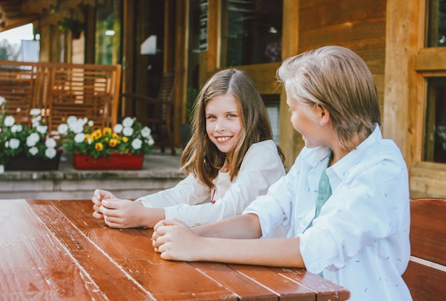 Attractive preteen blonde boy with sister sitting at the table in backyard of wooden cottage