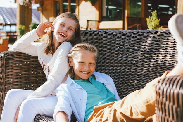 Привлекательные предподростковый сестра и брат, сидя на плетеном диване на заднем дворе деревянного коттеджа