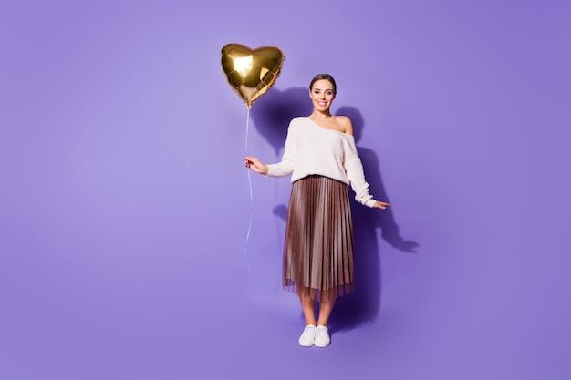 Привлекательная красивая очаровательная девушка держит в руке гелиевый шар