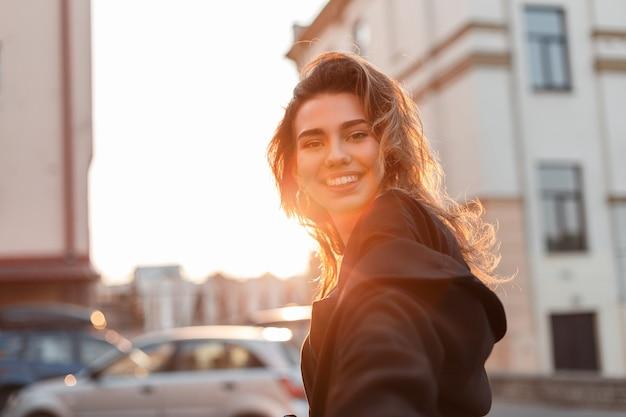 세련 된 옷에 매력적인 꽤 쾌활 한 젊은 여자는 밝고 화창한 날에 도시 주변을 산책합니다.