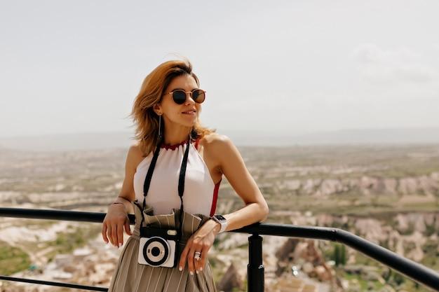 サングラスをかけ、レトロなカメラを持って目をそらし、山の風景に笑みを浮かべて飛んでいる髪を持つ魅力的なかわいい女の子