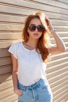 夏のヴィンテージサングラスでスタイリッシュな髪型を持つ魅力的なかなり若い流行に敏感な女性青いスタイリッシュなジーンズの白いtシャツは晴れた夏の日に木製の壁の近くでポーズをとる