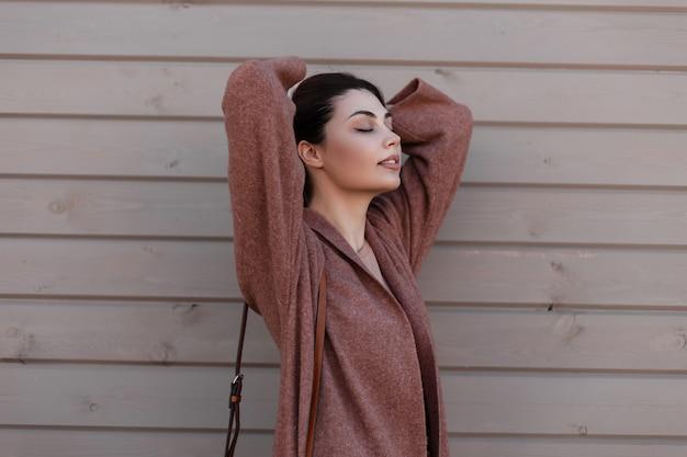 널빤지에서 빈티지 건물 근처 포즈 우아한 겉옷에 매력적인 예쁜 젊은 여자 패션 모델. 아름다운 사랑스러운 도시 세련된 소녀 모델은 머리카락을 곧게 펴고 나무 벽 근처에서 휴식을 즐깁니다.