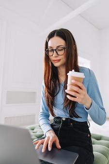 Привлекательная довольно молодая женщина в очках фрилансера, используя портативный компьютер дома