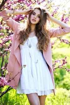 明るい白いドレスの魅力的なかなり若い女性