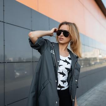 세련 된 블랙 선글라스에 세련 된 옷에 매력적인 예쁜 젊은 여자는 현대 회색 건물 근처 도시에서 포즈. 유럽 red-haired 소녀는 밝고 화창한 날을 즐깁니다.