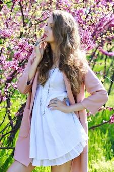 Attraente bella giovane donna in abito bianco chiaro