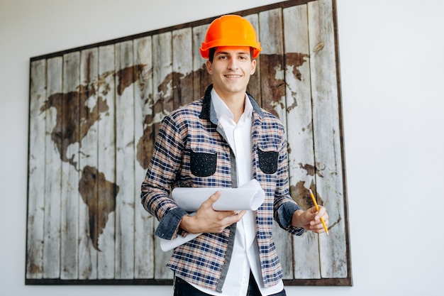 An attractive professional man in a helmet with a drawing in the office