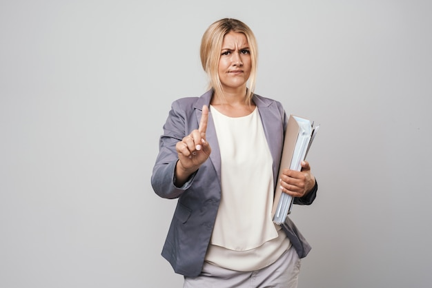 Attractive puzzled blonde haired angry businesswoman wearing jacket standing isolated over gray wall, carrying folders, pointing