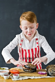An attractive red-haired boy in a chef's apron is cooking a hamburger in the kitchen.