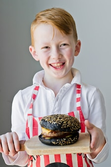 An attractive red-haired boy is holding a wooden chopping board with a hamburger.